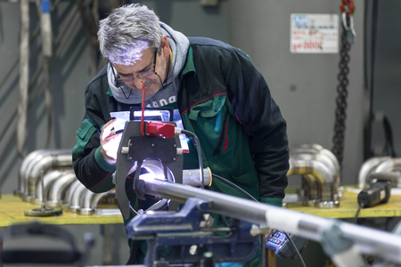 orbital: Industrial operator setting  computer controlled process of orbital welding machine in  stainless steel pipes manufacturing workshop.