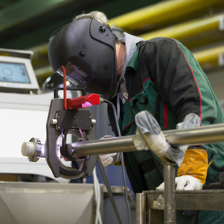 inox: Industrial operator setting  computer controlled process of orbital welding machine in inox pipes manufacturing workshop. Square composition.
