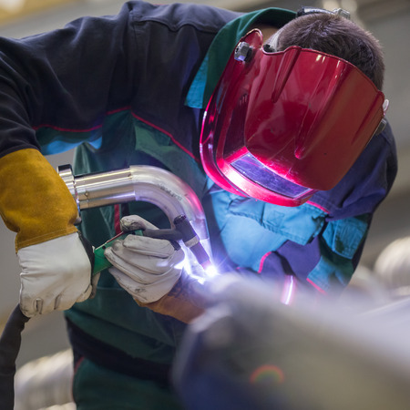 protective workwear: Industrial worker with protective mask welding inox elements in steel structures manufacture workshop. Stock Photo