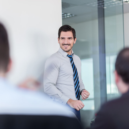 motivator: Relaxed cheerful team leader and business owner leading informal in-house business meeting. Business and entrepreneurship concept. Stock Photo