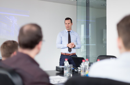 motivator: Business man making a presentation at office. Business executive delivering a presentation to his colleagues during meeting or in-house business training, explaining business plans to his employees. Stock Photo