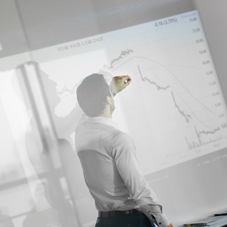 office presentation: Businessman making a presentation in front of whiteboard. Business executive delivering a presentation to his colleagues during meeting or in-house business training.