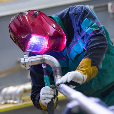 Industrial worker with protective mask welding inox elements in steel structures manufacture workshop. Archivio Fotografico