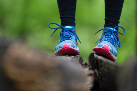 tree detail: Adventure, sport and exercise. Detail of female legs wearing sport shoes standing on tree trunk in forest.