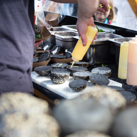 international food: Chef making  burgers outdoor on open kitchen international food festival event. Street food ready to serve on a food stall.