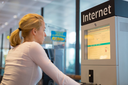access point: Young caucasian woman using comupter with public internet access point on airport.