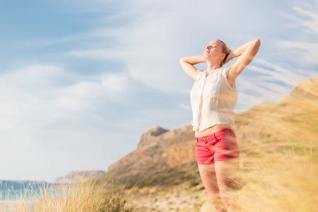 Relaxed vrouw, armen tiseerde, genieten van zon, vrijheid en het leven van een een prachtig strand. Jonge dame gevoel vrij, ontspannen en gelukkig.