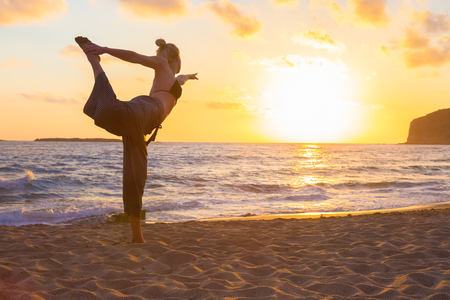 sandy beach: Silhouette of young woman practicing standing bow yoga pose on sandy beach at sunset. Stock Photo