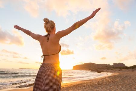 mujer relajada, con los brazos rised, disfrutando del sol, la libertad y la vida de una hermosa playa en la puesta del sol. Señora joven que se siente libre, relajado y feliz. Foto de archivo