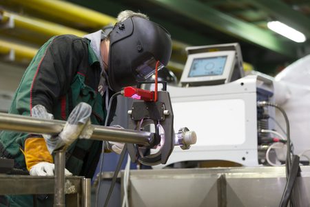 orbital: Industrial operator setting  computer controlled process of orbital welding machine in inox pipes manufacturing workshop. Stock Photo