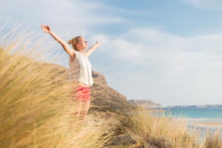 Relaxed kobieta, ręce twierdza, ciesząc się słońcem, wolność i życie jest piękna plaża. Młoda pani czuje się wolny, spokojny i szczęśliwy. Zdjęcie Seryjne
