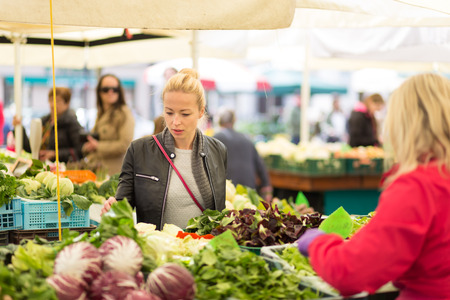 local: Woman buying fruits and vegetables at local food market. Market stall with variety of organic vegetable. Stock Photo