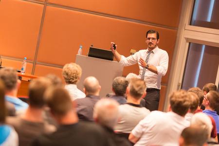 Spreker geeft een lezing in de conferentiezaal op zakelijke evenement. Publiek bij de conferentiezaal. Business and Entrepreneurship.