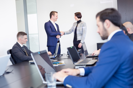 working hands: Sealing a deal. Business people shaking hands, finishing up meeting in corporate office. Businessman working on laptop in foreground. Stock Photo