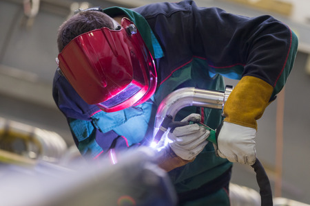 steel workers: Industrial worker with protective mask welding inox elements in steel structures manufacture workshop. Stock Photo