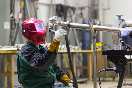 metalwork: Industrial worker with protective mask welding inox elements in steel structures manufacture workshop. Stock Photo