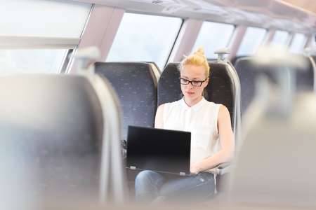 travel woman: Businesswoman sitting and traveling by train working on laptop. Business travel concept.