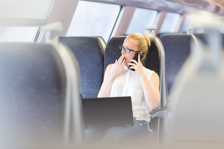 tiresome: Businesswoman traveling by train, yawning while talking on cellphone and working on laptop. Long and tiresome business travel concept.