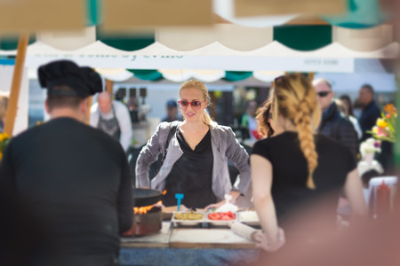 international food: Beautiful blonde caucasian lady buying freshly prepared meal at a local street food festival. Urban international kitchen event in Ljubljana, Slovenia, in summertime.