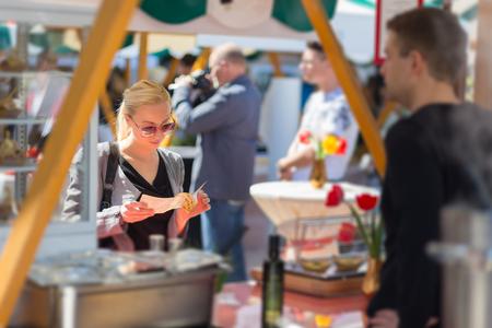 Mooie blonde Kaukasische dame het kopen van vers bereide maaltijd in een lokale straat eten festival. Urban internationale keuken evenement in Ljubljana, Slovenië, in de zomer.