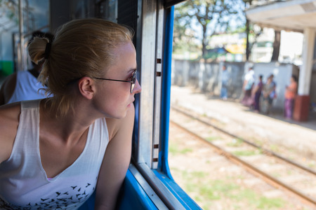 adventurer: Young female adventurer traveling by train in Asia, waching local people through big window.