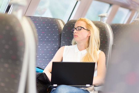 sitted: Businesswoman naping sitted while traveling by train and working on laptop. Tiresome business travel. Stock Photo
