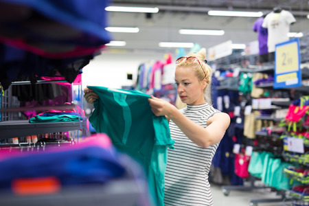merchandise: Beautiful caucasian woman shopping sportswear in sports store.