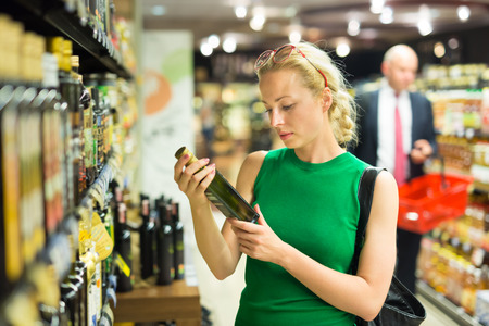 Mooie blanke vrouw winkelen boodschappen bij de supermarkt.