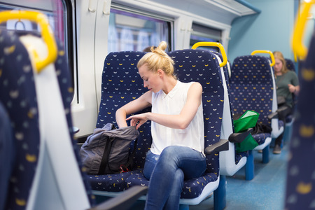 woman bag: Young woman searching something in her bag while traveling by train.