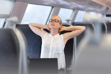 Imprenditrice viaggia in treno, streching sul suo sedile mentre si lavora sul computer portatile. concetto di viaggio business.