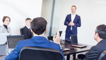 business conference: Colleague asking a question to  businessman during a presentation. Successful team leader and business owner  leading informal in-house business meeting. Business and entrepreneurship concept.