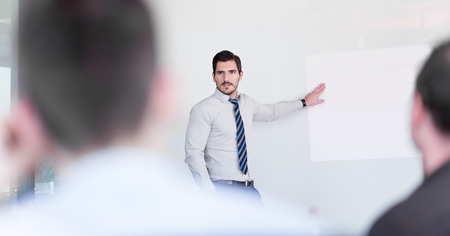 Business man making a presentation at office. Business executive delivering a presentation to his colleagues during meeting or in-house business training, explaining business plans to his employees. Banque d'images