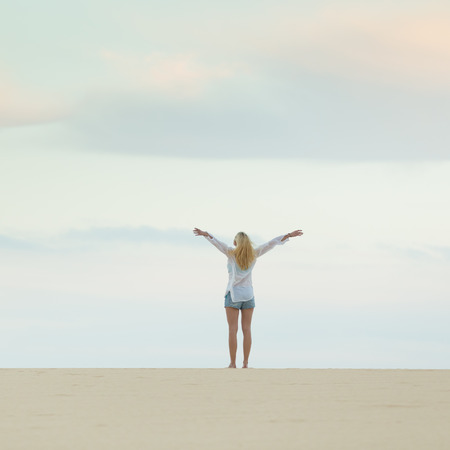 elated: Relaxed woman enjoying freedom feeling happy at beach at dusk. Serene relaxing woman in pure happiness and elated enjoyment with arms raised outstretched up.