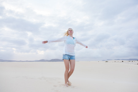 elated: Relaxed woman enjoying freedom feeling happy at beach in the morning. Serene relaxing woman in pure happiness and elated enjoyment with arms outstretched. Copy space. Stock Photo