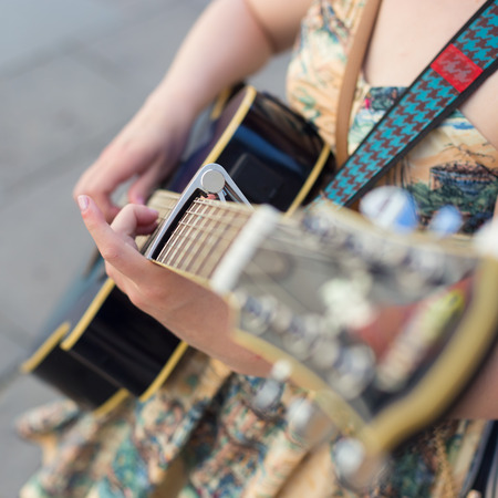 acoustical: Female street musician playing guitar on sidewalk. Stock Photo