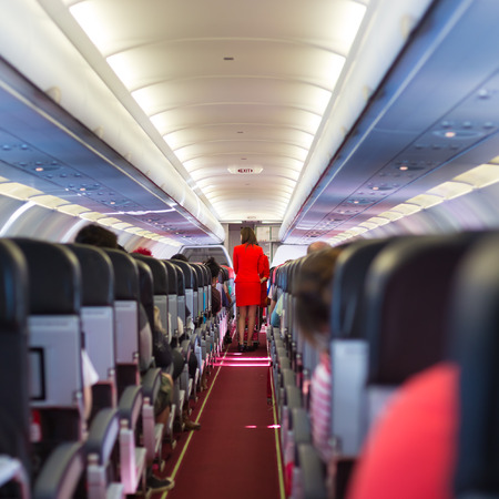 Interior of airplane with passengers on seats and stewardess in red uniform walking the aisle. Stockfoto
