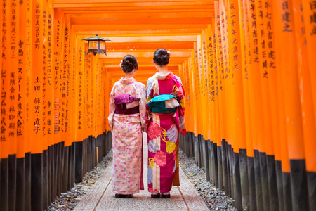 Two geishas among red wooden Tori Gate at Fushimi Inari Shrine in Kyoto, Japan. Selective focus on women wearing traditional japanese kimono. Éditoriale
