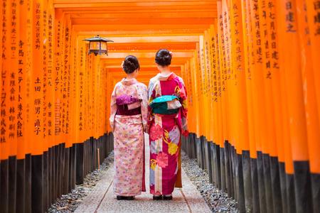 Two geishas among red wooden Tori Gate at Fushimi Inari Shrine in Kyoto, Japan. Selective focus on women wearing traditional japanese kimono. Editorial
