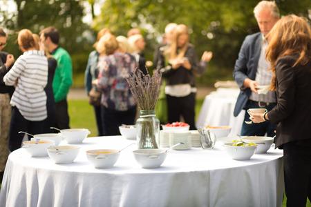 Banchetto pausa pranzo in conferenza sulla terrazza dell'hotel. Assortimento di alimenti e bevande. persone non riconoscibile che parlano per il cibo in background. Archivio Fotografico