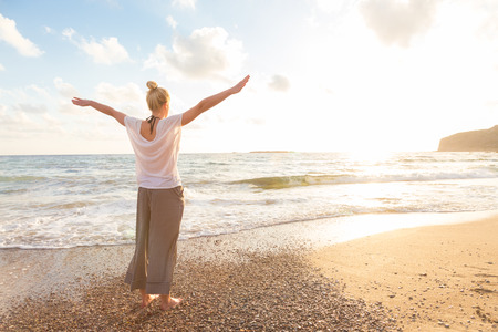 freedom: Relaxed woman, arms rised, enjoying sun, freedom and life an beautiful beach in sunset. Young lady feeling free, relaxed and happy. Concept of vacations, freedom, happiness, enjoyment and well being.