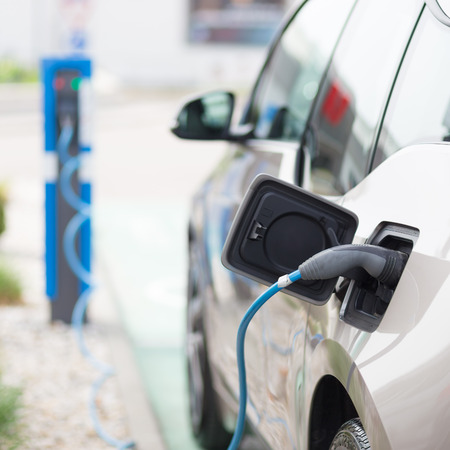 Power supply for electric car charging.  Electric car charging station. Close up of the power supply plugged into an electric car being charged. Stock Photo - 63929135
