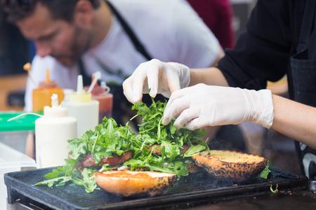요리사 야외 오픈 키친 국제 음식 축제 이벤트에 쇠고기 햄버거를 만들기. 음식 거리에서 봉사 할 준비가 거리 음식.
