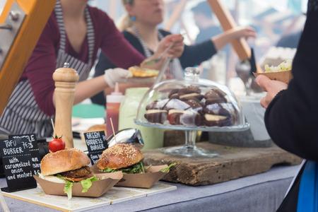 Tofu hamburguesas vegetarianas siendo atendidos en el puesto de comida en la cocina abierta evento internacional festival de comida de comida de la calle.
