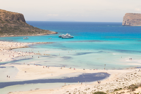 beach panorama: Breathtaking panorama of Balos beach and lagoon and Gramvousa island on Crete, Greece. Tourist boats mooring in lagoon. Stock Photo