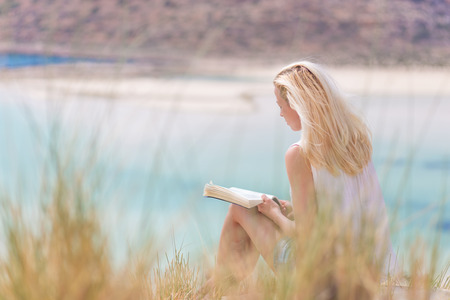 Relaxed woman enjoying sun, freedom and good book an beautiful sandy beach of Balos in Greece. Young lady reading, feeling free and relaxed. Vacations, freedom, happiness, enjoyment and well being. Stock Photo