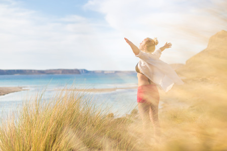 sea grass: Relaxed woman in white shirt, arms rised, enjoying sun, freedom and life an beautiful beach. Young lady feeling free, relaxed and happy. Concept of vacations, freedom, happiness, joy and well being.