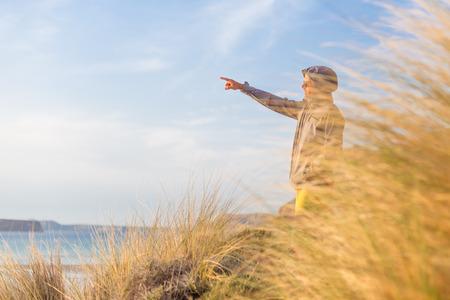 duna: hombre activo deportivo señalar la mano en el horizonte, disfrutando de la belleza de la naturaleza, la libertad y la vida, en el precioso paisaje. estilo de vida activo al aire libre.