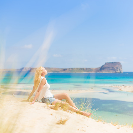 Relaxed woman enjoying sun, freedom and life an a beautiful sandy beach of Balos in Greece. Young lady feeling free, relaxed and happy. Vacations, freedom, happiness, enjoyment and well being.