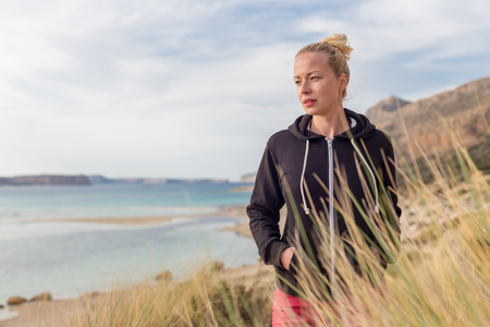 a serene life: Relaxed woman in dark hoodie and colorful scarf looking at distance, enjoying beautiful nature, freedom and life at serene landscape at Balos beach, Greece. Concept of well being. Stock Photo