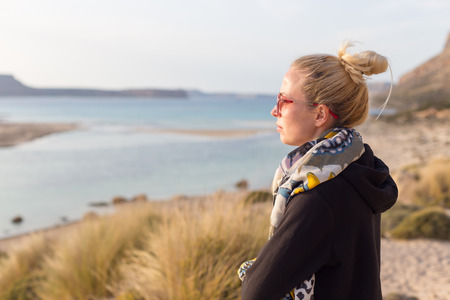 serene landscape: Relaxed woman in dark hoodie and colorful scarf looking at distance, enjoying beautiful nature, freedom and life at serene landscape at Balos beach, Greece. Concept of well being. Stock Photo